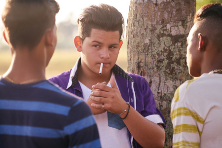 Youth culture, young people, group of male friends, mixed race teen outdoor, teenager in park. Hispanic kid smoking cigarette, confident boy, smoker. Health problems, social issues. 版權商用圖片 - 58988401