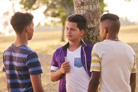 Jeugdcultuur, jongeren, groep mannelijke vrienden, multi-etnische tieners buitenshuis, multiraciale jongens samen in het park. Kinderen roken elektronische sigaret, e-sigaret rokers. Gezondheidsproblemen, sociale kwesties