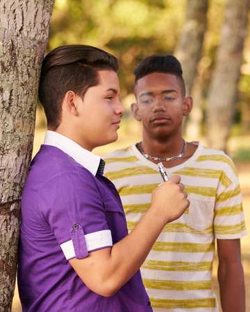 people problems: Youth culture, young people, group of male friends, multi-ethnic teens outdoors, multiracial boys together in park. Kids smoking electronic cigarette, e-cig smokers. Health problems, social issues
