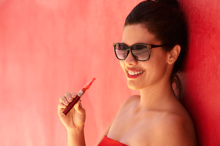 e pretty: Young hispanic people smoking e-cig, pretty sensual latina woman with electronic cigarette, happy sexy girl with sunglasses smiling and blowing smoke. Portrait looking at camera Stock Photo