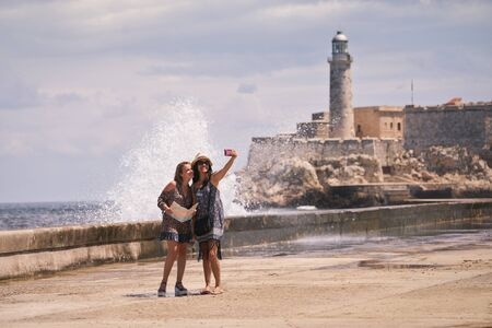 mobile telephone: Female friends on holiday, people traveling, young women having fun for vacations, happy girls smiling in Havana, Cuba. Persons taking selfie with camera phone, smartphone, mobile telephone picture Stock Photo