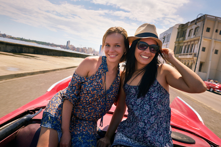 Female friends on holidays, people traveling, young women having fun on vacation, two happy girls smiling in Havana, Cuba. Hispanic persons laughing on old classic convertible car. Slow motion Фото со стока