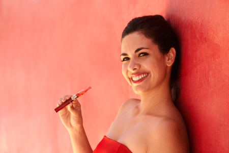 sexy girl smoking: Young hispanic people smoking e-cig, pretty sensual latina woman with electronic cigarette, happy sexy girl smiling and leaning on red wall with copy space. Portrait looking at camera