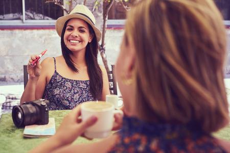 fiestas electronicas: amigas sobre vacaciones, jóvenes mujeres felices sienta en la barra fuma el cigarrillo electrónico. Foto de archivo