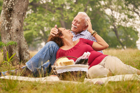 weekend activity: Senior couple, old man and woman in park on weekend activity. Grandpa and grandma doing picnic in wood. Concept of retirement age and love.
