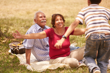 Old people, senior couple, elderly man and woman. Outdoor family having fun with happy grandpa and grandma hugging boy at picnic in park. Standard-Bild