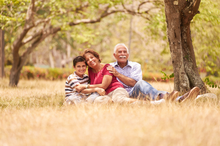 Old people, senior couple, elderly man and woman. Outdoor family having fun with happy grandpa and grandma hugging boy at picnic in park. Stock Photo