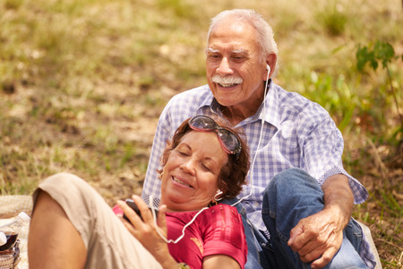 Old people, senior couple, elderly man and woman in park. Grandpa and grandma listening to song, music with mp3 player Stock Photo