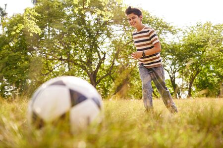 Adolescence and leisure activity. Young kid playing soccer in park, running towards the ball, smiling happy.