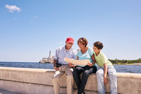 grandpa and grandma: Happy tourist family on holidays, during vacation journey in Cuba. Hispanic grandpa, grandma and grandson traveling in Havana reading a city map on the Malecon