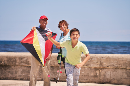 grandpa and grandma: Happy tourist family on holidays in Cuba. Hispanic grandpa, grandma and grandson having fun near the sea. Boy and grandparents running and playing with kite Stock Photo