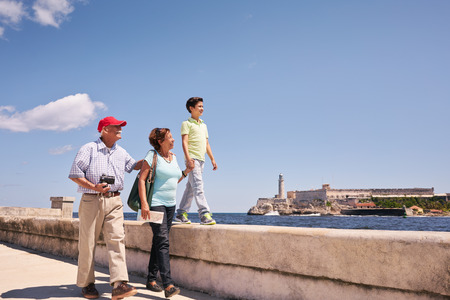 grandpa and grandma: Happy tourists on holidays in Havana, Cuba. Hispanic family with grandpa, grandma and grandson traveling and walking together on the Malecon Stock Photo