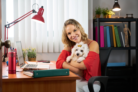 inseparable: People, pets and love for animals. Woman at home in office room works on laptop holding her little dog. She turns to the camera smiling.