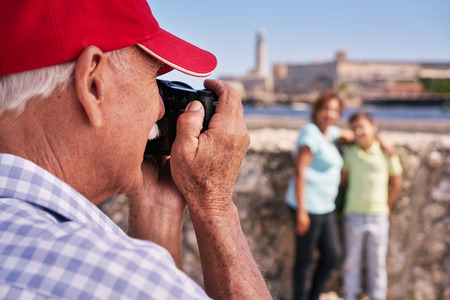 vacationing: Happy tourists on holidays. Hispanic people traveling in Havana, Cuba. Grandfather, grandmother and grandchild during summer travel, with senior man taking photos with camera