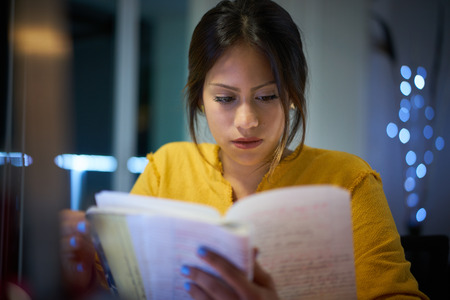 Young woman doing homework at night. Tired hispanic girl and college education. Female student studying for next day exam Foto de archivo