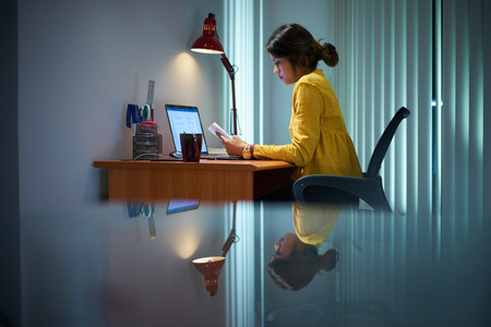 essay: Young woman with laptop computer for homework. Tired hispanic girl and college education. Female student studying and using pc at home Stock Photo