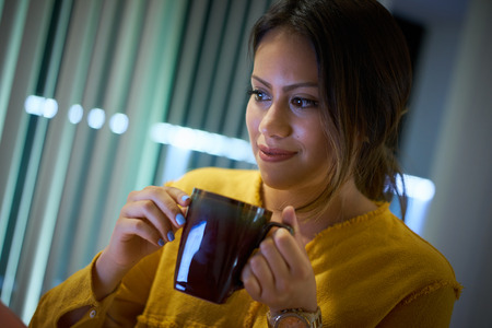 night school: Young beautiful hispanic woman drinking coffee at home. Girl studying late at night. College student doing education homework for school Stock Photo