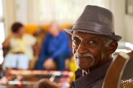 백그라운드에서 친구의 그룹과 함께 은퇴 가정에서 카메라를 찾고 노인 흑인의 초상화. 노인들을위한 호스피스에서 편안한 환자.
