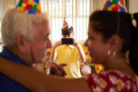 three generations of women: Family celebrating senior man birthday in retirement home. Patient dancing with daughter in hospital and child taking photo. Stock Photo