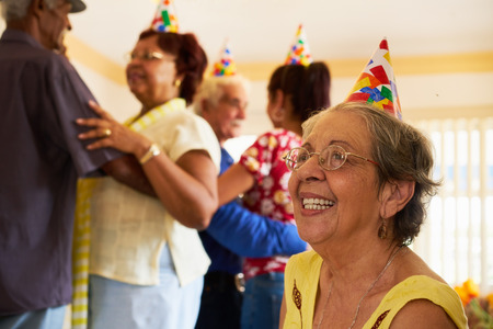 Group of old friends and family celebrating senior birthday party in retirement home. Patient woman smiling in hospice. Archivio Fotografico