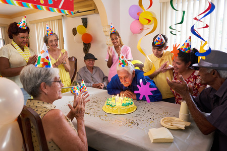 Group of old friends and family celebrating senior man 80 birthday party in retirement home. Happy elderly people having fun. Grandfather blowing candles on cake. Stock Photo