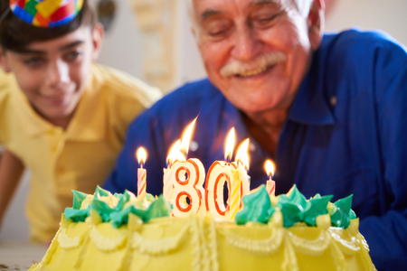 Grandson and family celebrating senior man eighty birthday. Grandfather blowing candles with number 80 on cake and smiling.