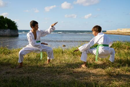 punched out: Children doing combat and extreme sports. Latino boys exercising in karate and traditional martial arts. Simulation of fight on the beach