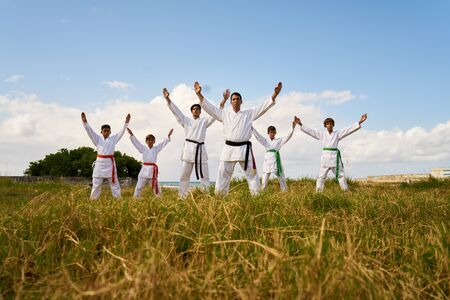 punched out: Hispanic men and children exercising in karate and traditional martial arts. Simulation of fight on the beach near the sea