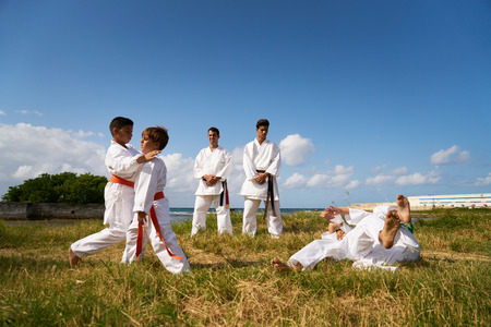 punched out: Combat and extreme sports, hispanic men and children exercising in karate and traditional martial arts. Simulation of fight on the beach