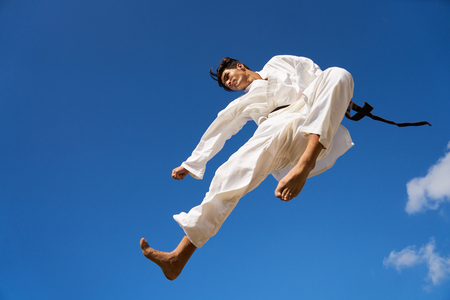 young male: Young people, athlete, sport activity, combat and extreme sports. Hispanic man exercising in karate and traditional martial arts, jumping mid-air in the sky