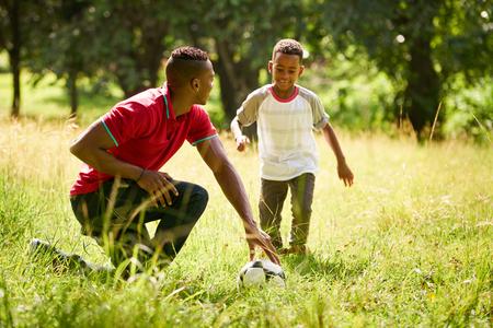 Gelukkig zwarte mensen doen sport praktijk in stadspark. Afro-Amerikaanse familie met vader onderwijs zoon hoe om te voetballen.