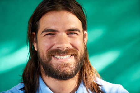 smile close up: Real Cuban people and feelings, portrait of happy young hispanic man with beard and long hair from Havana, Cuba, looking at camera and smiling