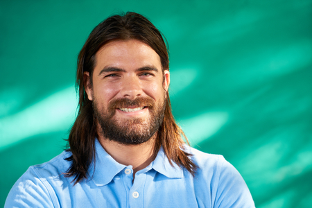 look latino: Real Cuban people and feelings, portrait of happy young hispanic man with beard and long hair from Havana, Cuba, looking at camera and smiling