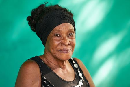 古いキューバの人々 と感情、カメラを見て幸せな上級アフリカ系アメリカ人女性の肖像画。背景の緑の壁上の領域をコピーします。