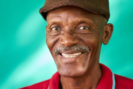 Real Cuban people and feelings, portrait of happy senior african american man looking at camera. Cheerful old latino grandfather with mustache and hat from Havana, Cuba Stock Photo