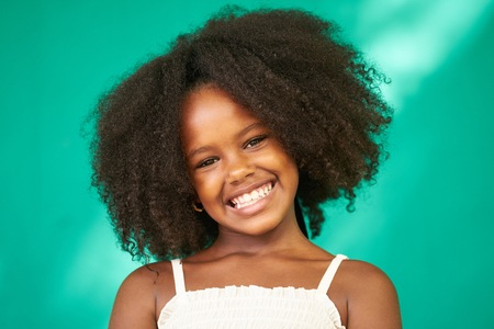 Portrait of Cuban children with emotions and feelings. Black young girl from Havana, Cuba smiling, looking at camera with joyful and funny expression.