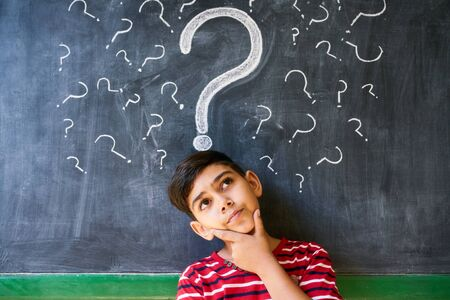thoughts: Concepts on blackboard at school. Hispanic boy with doubts and thoughts in class. Portrait of male child thinking against question marks on blackboard Stock Photo