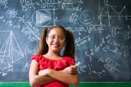 Concepts on blackboard at school. Young people, students and pupils in classroom. Smart hispanic girl writing math formula on board during lesson. Portrait of female child smiling, looking at camera Stockfoto