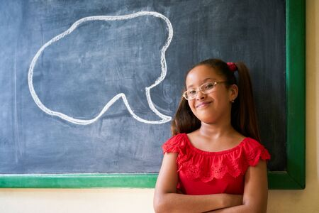 latina girl: Concept on blackboard at school. Happy and funny latina girl in class, leaning on blackboard. Portrait of female child looking at camera with drawing of cloud in background Stock Photo