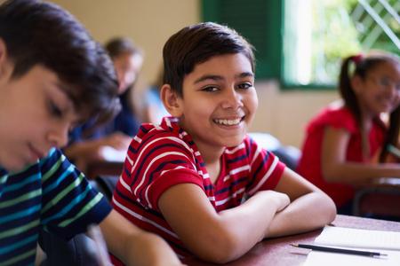 Jongeren en onderwijs. Groep van Spaanse studenten in de klas op school tijdens de les. Gelukkige jongen lacht en zit op bureau