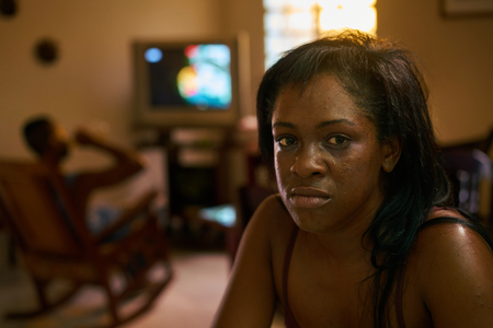 Social issue, abuse and violence on women, drunk hispanic man and sad black woman crying at home. Violent husband and abused wife Archivio Fotografico