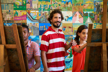 School of art, college of arts, education for group of young students. Portraif of happy latino professor smiling, man working as teacher and looking at camera.