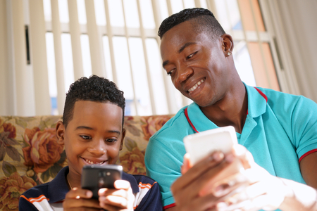 young boys: Happy black family at home. African american father and child playing game with cell phone. Hispanic dad and son having fun with smartphone. Stock Photo