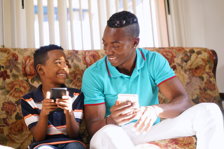 Happy black family at home. African american father and child playing game with cell phone. Hispanic dad and son having fun with smartphone. Stock Photo