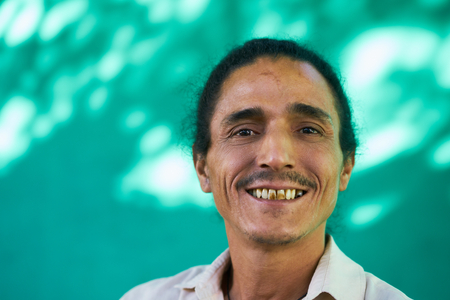 Real Cuban people and feelings, portrait of happy hispanic man with goatee and long hair from Havana, Cuba looking at camera, laughing and smiling