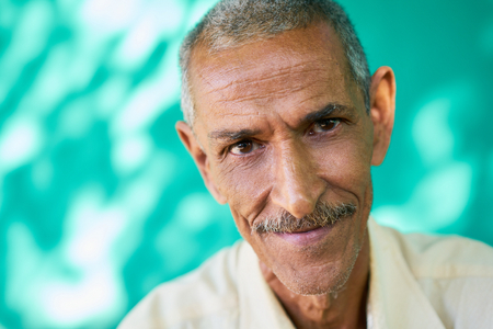 Real Cuban elderly people and feelings, portrait of happy old hispanic man with mustache from Havana, Cuba looking at camera and smiling Stock Photo