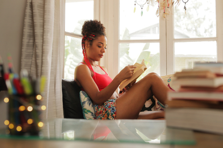 Happy female student reading book and sitting on sofa. Young african american woman relaxing, black girl lying on couch. Hispanic people and lifestyle, leisure and relaxation at home Banco de Imagens