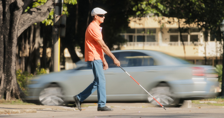 visually: Hispanic blind man, latino people with disability, handicapped person and everyday life. Visually impaired man with walking stick, crossing the street with cars and city traffic Stock Photo