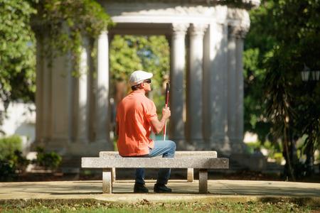 Spaanse blinde man, Latino mensen met een handicap, gehandicapte persoon en dagelijks leven. Visueel gehandicapte man met stokje, zittend op bankje in het stadspark