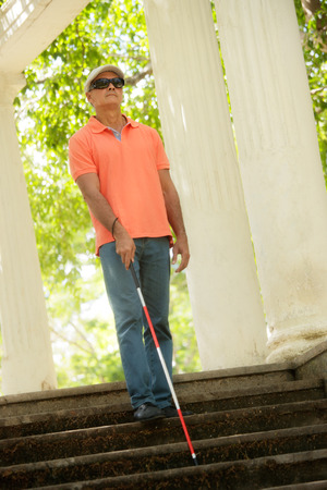 Hispanic blind man, latino people with disability, handicapped person and everyday life. Visually impaired man with walking stick, descending steps in city park Stock Photo